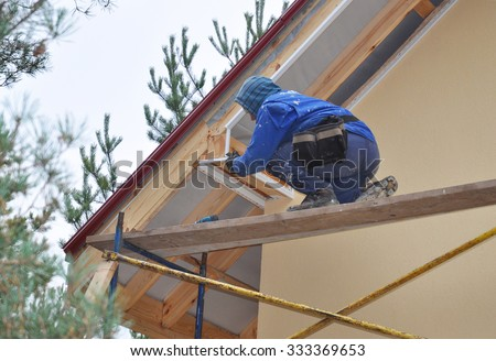 Roofer on the Corner of House  Install Soffit. Roofing Construction. Soffit and Fascia is Usually Constructed of Vinyl, Wood or Aluminum and is Installed on the Underside of Roof Overhangs and Eaves. - stock photo