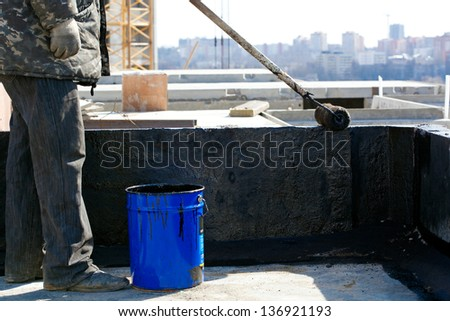 Roofer worker painting black coal tar or bitumen at concrete surface by the roller brush - stock photo