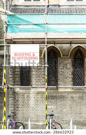 Roofing and Scaffolding sign for repairs of an old building closeup - stock photo