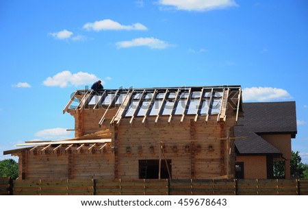 Roofing Construction and Building New Wooden House Exterior. Constructor, Roofer Install, Repair Asphalt Shingles on the Rooftop Outdoor. Roofing shingles installation. - stock photo
