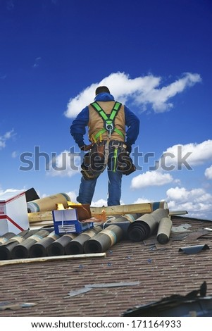 Roofing Contractor on the Roof Repairing. Contractor Repairing Damage to Shingles. Roofing Works - stock photo