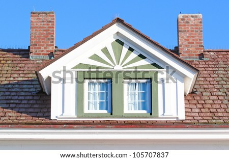 Roofline showing loft window and twin chimneys - stock photo