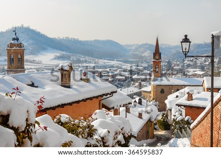 Roofs and churches covered with white snow in small town of Corneliano d'Alba in Piedmont, Northern Italy. - stock photo
