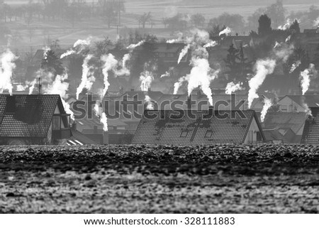 roofs and smoking chimneys in wintertime - stock photo