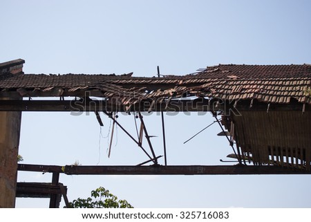 Rooftop decaying with blue sky behind and old structures - stock photo