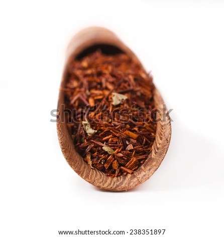 Rooibos tea in a wooden scoop isolated on white background  - stock photo