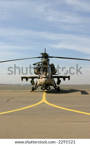 Rooivalk helicopter pre-flight standing on apron with cloudy background - stock photo