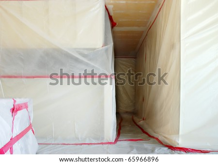 Room covered with clear plastic sheeting after asbestos abatement completed on popcorn ceiling - stock photo