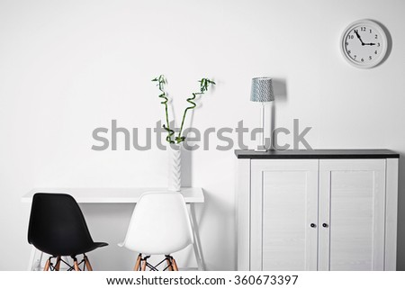 Room interior with commode, chairs and table on white wall background - stock photo