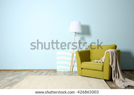 Room interior with green armchair on blue wall background - stock photo