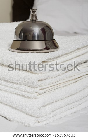 Room service bell and towels on bed - stock photo