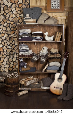 room with a cupboard with knitted clothes and books in a village house - stock photo