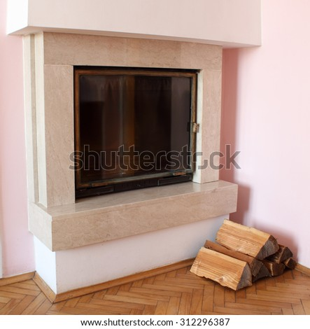 Room with fireplace and firewood - stock photo