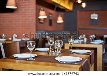 Room with served tables in restaurant, focus on glass in center - stock photo