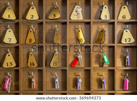 Rooms keys at a two stars hostel reception desk counter. - stock photo