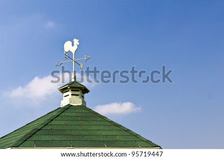 Rooster weather vane on roof and blue sky background - stock photo