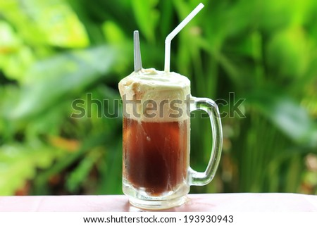 Root beer float a tasty summer treat on Green tree background - stock photo