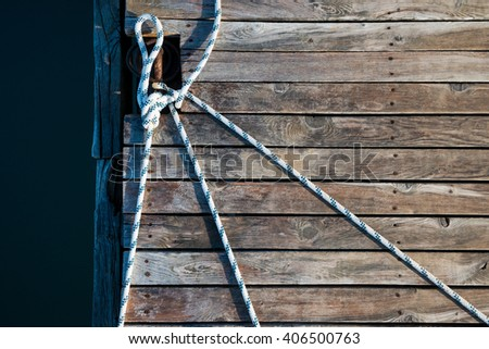 rope and old boards background on the pier in the bay - stock photo