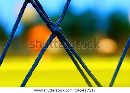 Rope barrier turf football field : focus on the knot : This image was intended to have a shallow depth of field : for use in the background .  - stock photo