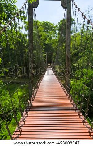 rope bridge or suspension bridge in forest at Khao Kradong Forest Park in Buriram Province,THAILAND. - stock photo