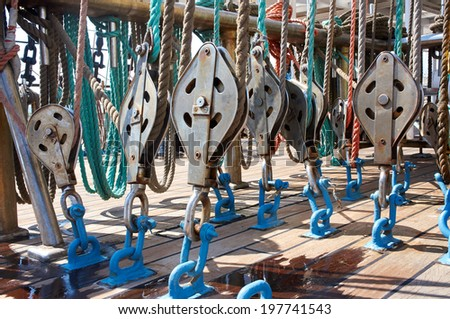 Rope control the sails, tied to a wooden beam, on sailboat - stock photo