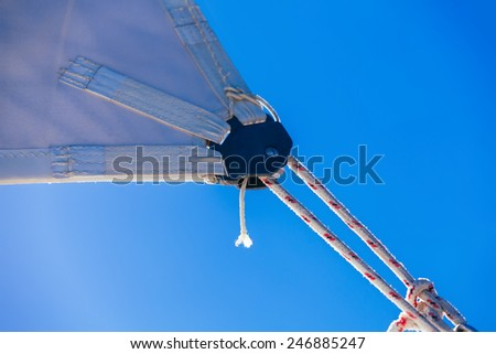 rope, knot and piece of sail isolated on blue on sailing boat  - stock photo