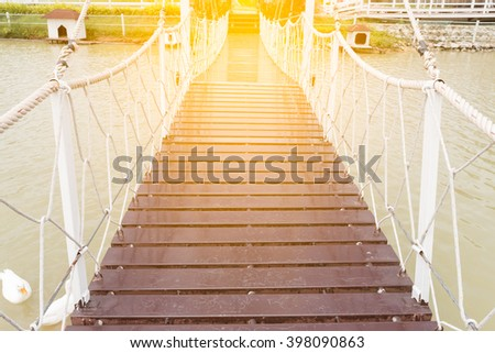 Rope walkway through the river with light. - stock photo