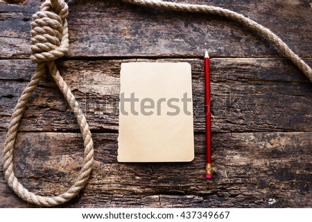 rope with a slipknot and a suicide note - stock photo