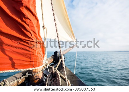 rope wound on a wooden cleat fixed on the hull of a rigging vintage sailing boat with a beige jib and an ocher sail filled by the wind at the blur background during a sunny sea trip in brittany - stock photo