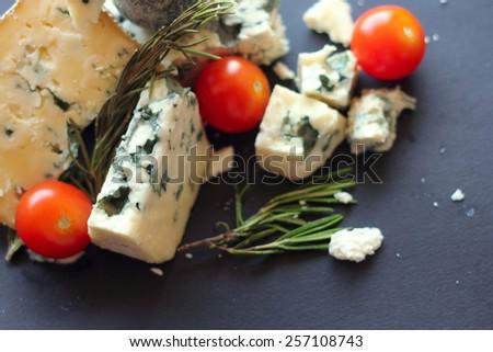 Roquefort cheese composition on dark background - stock photo