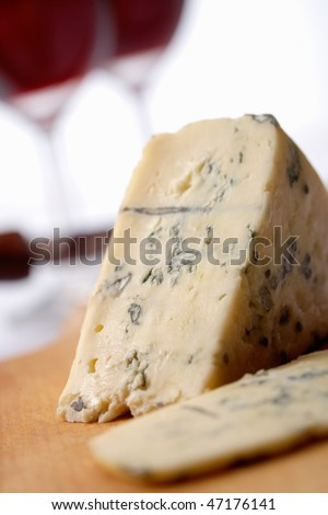Roquefort soft blue french cheese.  A wine at background - stock photo