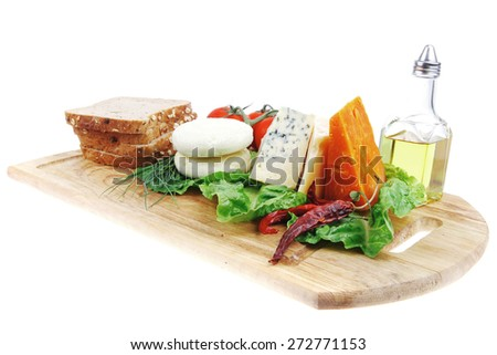 roquefort with cheddar, parmesan and soft feta cheese on wooden board with tomatoes bread and olive oil isolated over white background - stock photo