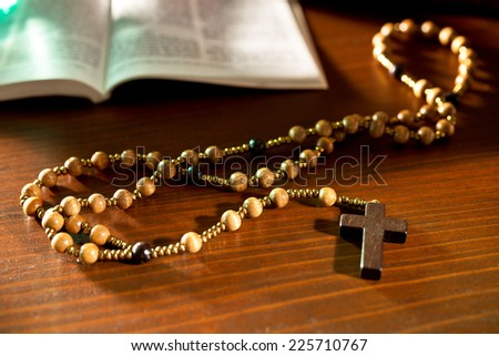 rosary and bible on the wooden table - stock photo