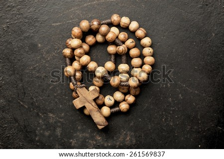 rosary beads on old black background - stock photo