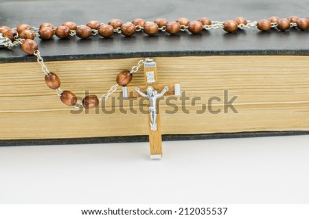 Rosary beads on old copy of the Bible - stock photo