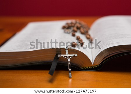 Rosary beads resting on open bible on wooden table - stock photo