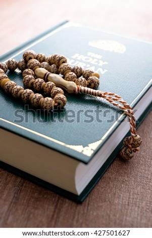 Rosary on Holy Quran - stock photo