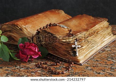 Rosary, red rose and old holy bible - stock photo