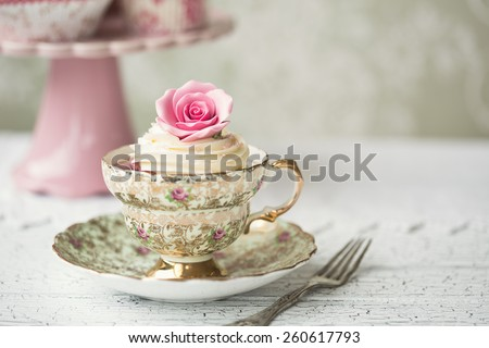 Rose cupcake in a vintage teacup - stock photo