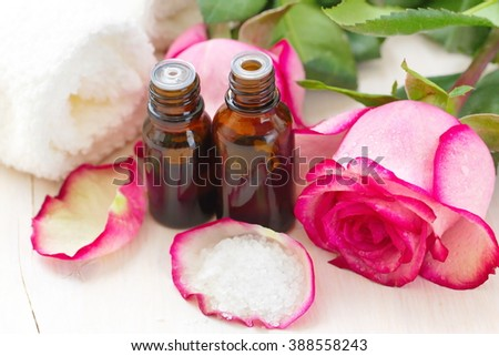 Rose essential aroma oil, sea salt and fresh flowers - stock photo