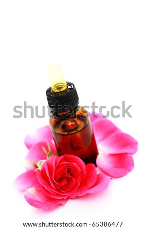 rose essential oil with rose petals on white - beauty treatment - stock photo
