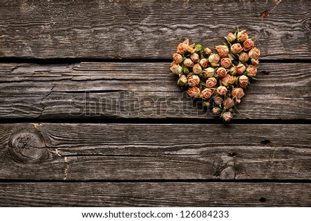 Rose flowers in heart shape on old wooden plates. Sweet holiday background - stock photo