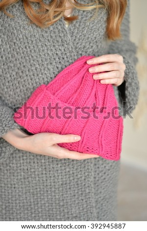 Rose knitted cap in her hand - stock photo