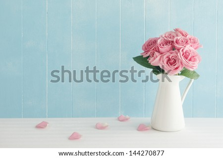Rose placed on the desk in blue background - stock photo