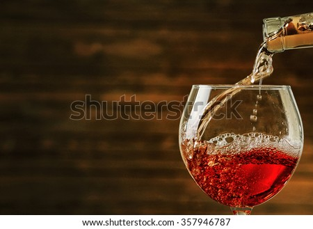 Rose wine pouring in glass on wooden background - stock photo