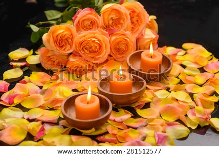 Rose with many rose petals with candle in bowl  - stock photo