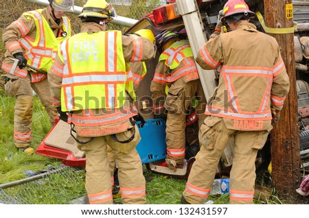 ROSEBURG, OR - MARCH 19: Emergency workers extricate a victim from a single car, rollover accident during a spring rain in Roseburg Oregon, March 19, 2013 - stock photo