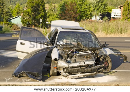 ROSEBURG, OR, USA - MAY 30, 2014: Police and fire fighters survey the scene of a single vehicle accident due to excessive speed sends the driver to the hospital in Roseburg, OR, on May 30, 2014 - stock photo
