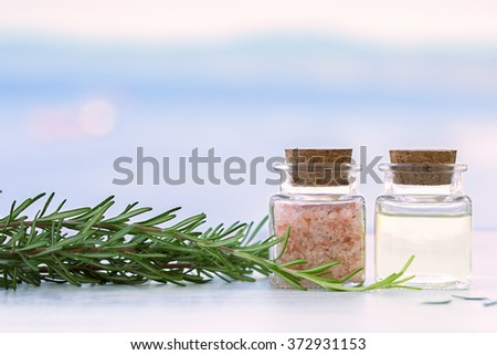 Rosemary aromatherapy essential oil and salt in bottles on sunset - stock photo