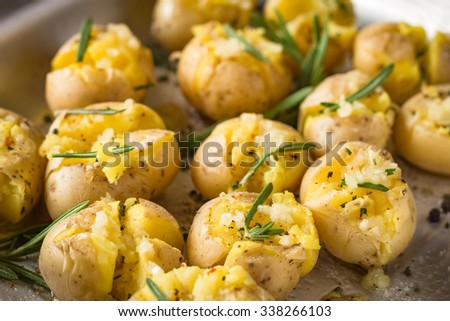 Rosemary baked potatoes with garlic and sea salt on baking tray, close up. Cooked side dish for Christmas table - stock photo